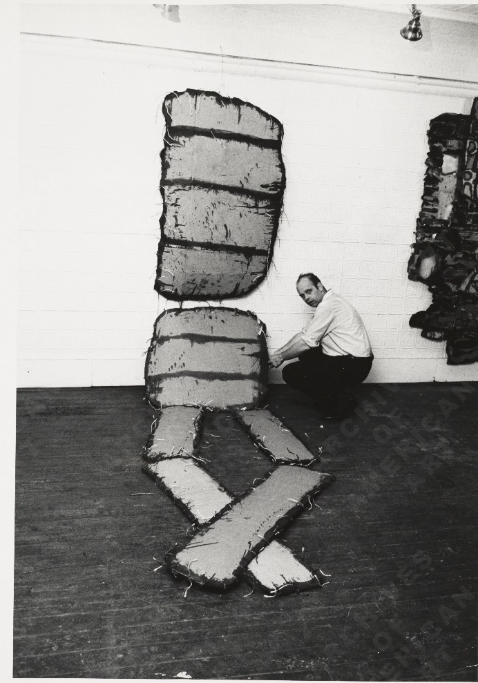 Claes Oldenburg and one of his works in his show The Street at the Reuben Gallery, 1960 Photo by Charles Rapoport